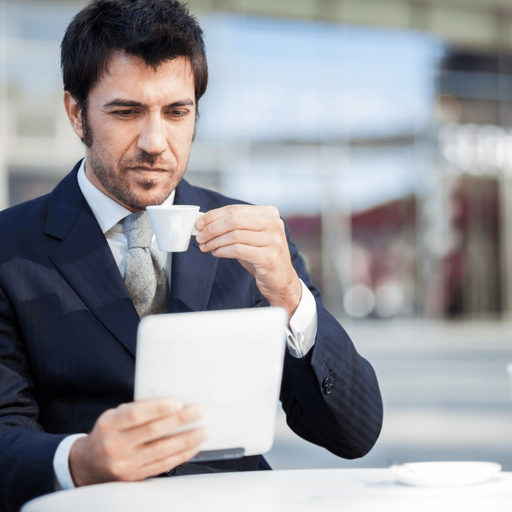 Business man reading on tablet with espresso in hand